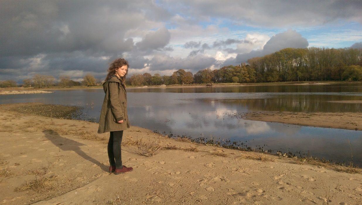 Eine junge Besucherin des Flusshofs steht am herbstlichen Elbstrand