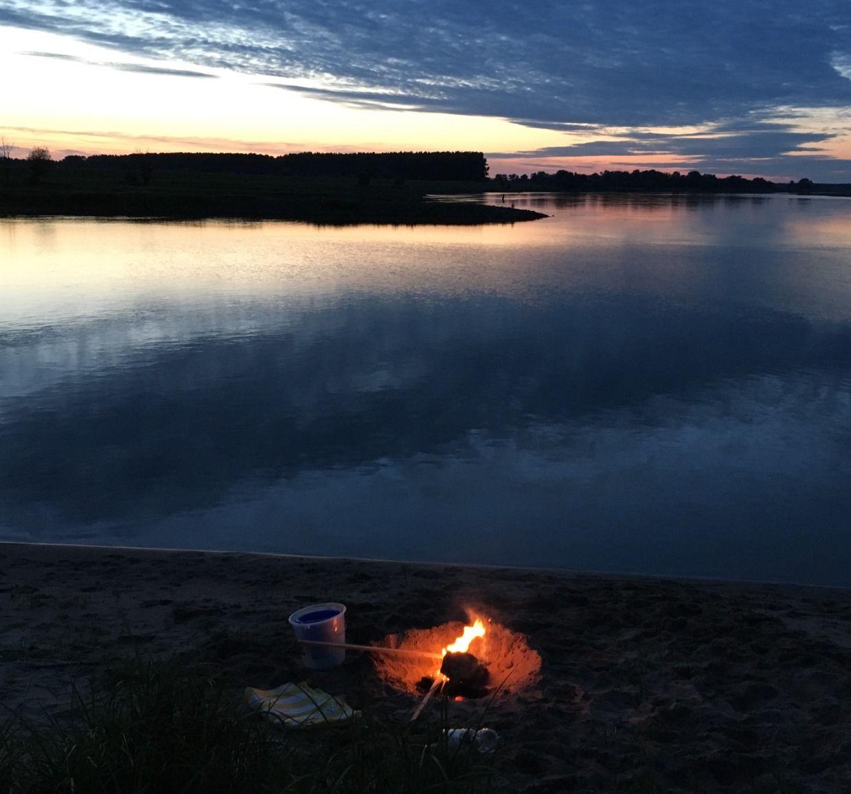 Lagerfeuer am Elbstrand mit der Elbe in der Dämmerung im Hintergrund, in der Nähe des Flusshofs.